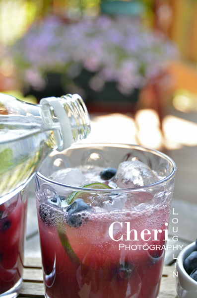 Blueberry Peach Mojito Adding Club Soda Topper 090: Outdoor Entertaining set-up for Driscoll's Blueberry Peach Mojito cocktail recipe – Cheri Loughlin is The Intoxicologist, a corporate mixologist who creates and photographs the best cocktails and mixed drinks for home entertaining and bar use.