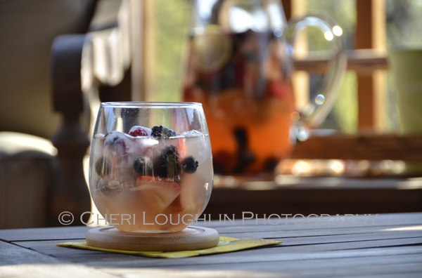 The berries soaked up quite a bit of the alcohol in the marinating process. To distribute the flavor I placed about 1/3 cup of berries in a goblet and very lightly mashed them with the back of a spoon. All the Beautiful Berries Sangria recipe and photo by Mixologist Cheri Loughlin, The Intoxicologist