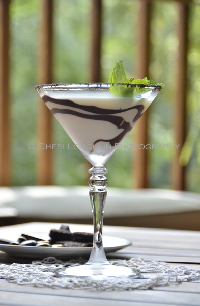 Chocolate Mint Cookie Cocktail 052 with Creme de Menthe Liqueur, Cake Vodka, Chocolate Vodka, Creme de Cacao, Half & Half with crushed Oreo cookie rim, chocolate swirl and mint leaf garnish. - recipe and photo by Mixologist Cheri Loughlin, The Intoxicologist